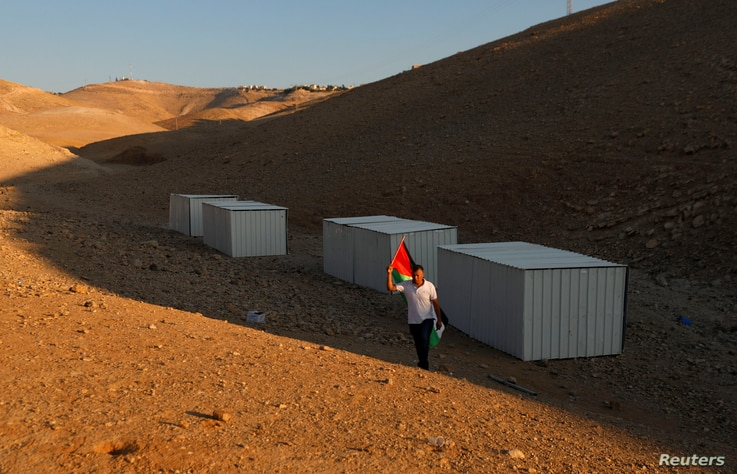 A man holds a Palestinian flag as he walks near shacks installed by activists to protest the Israeli plan to demolish the Bedouin village of Khan al-Ahmar, in Khan al-Ahmar, occupied West Bank, Sept. 11, 2018.