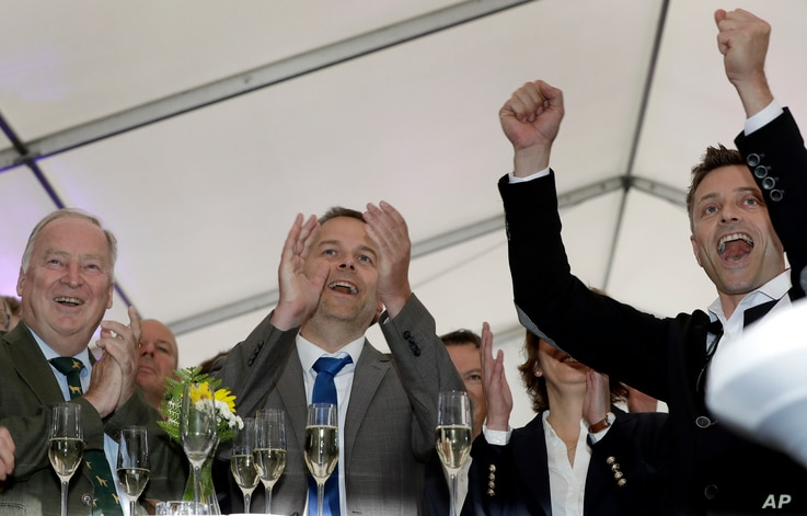 Germany Election: AfD member Alexander Gauland, left, and Leif-Erik Holm, center, top candidate of the AfD, celebrate at the gathering of the AfD (Alternative for Germany) party in Schwerin, Germany, Sunday, Sept. 4, 2016 after the state elections in...