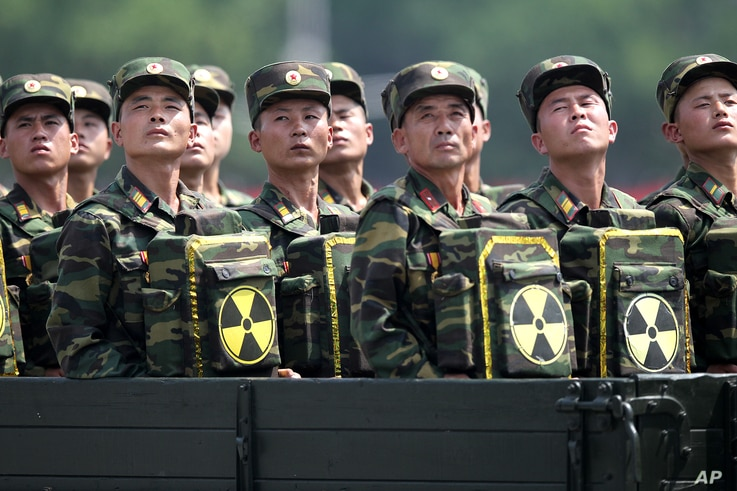 FILE - North Korean soldiers, carrying packs marked with a nuclear symbol, turn and look toward leader Kim Jong Un as they parade during a ceremony marking the 60th anniversary of the Korean War armistice in Pyongyang, North Korea, July 27, 2013. The...
