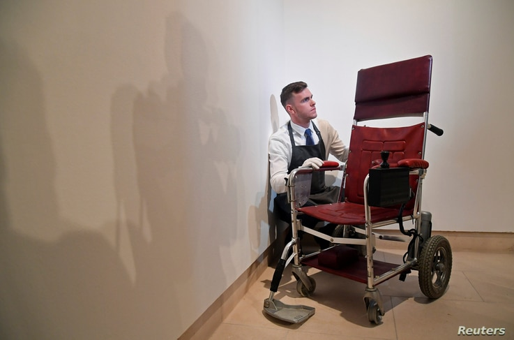 Fine-art handler Tom Richardson poses with a motorised wheelchair belonging to British theoretical physicist Stephen Hawking ahead of an auction of items from Hawkings' personal estate at Christie's in London, Britain, Oct. 30, 2018.