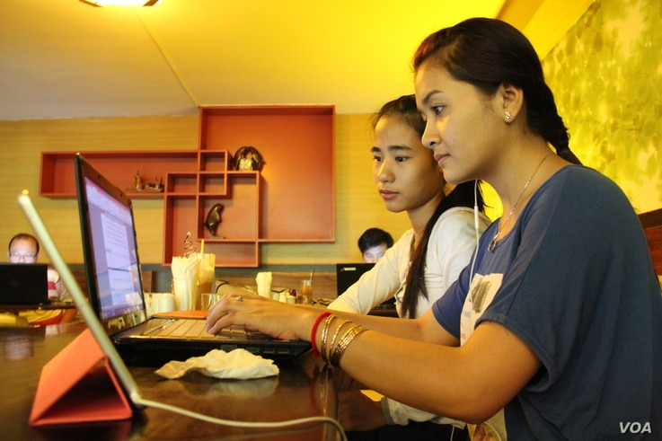 University students from the Royal University of Phnom Penh check the Internet in a coffee shop along the city's Russian Federation Boulevard, June 13, 2014. A leaked cybercrime draft law has increased concerns from human rights activists that the la...