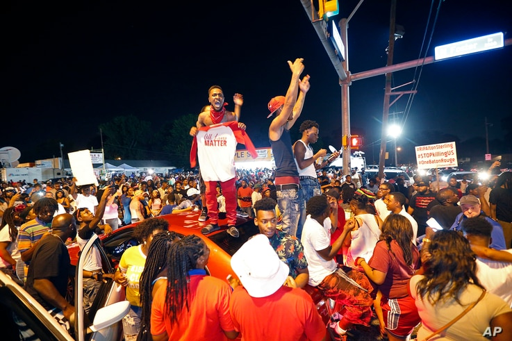 Protesters stand on cars as they congregate at N. Foster Dr. and Fairfields Ave., the location of the Triple S convenience store in Baton Rouge, La., Wednesday, July 6, 2016.