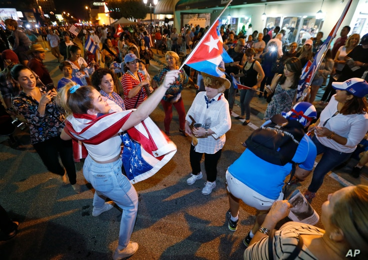 Members of the Cuban community dance in the street as they react to the death of Fidel Castro in front of the Versailles Restaurant in the Little Havana neighborhood of Miami, Nov. 26, 2016.