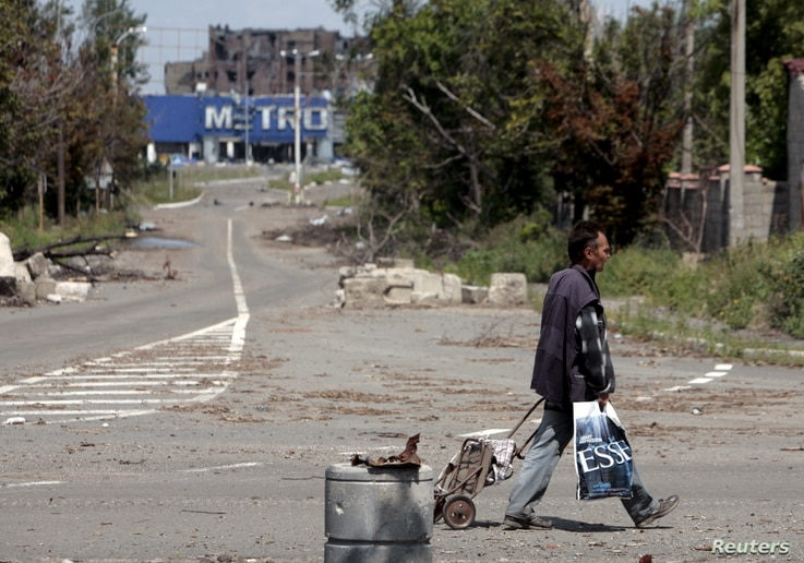 A man with a cart walks in a street in rebel-controlled Donetsk, Ukraine, July 18, 2015.