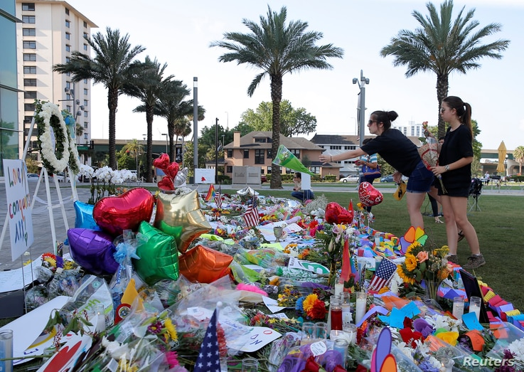 A woman throws a bouquet of flowers at a memorial for the victims of the shooting at the Pulse gay nightclub in Orlando, Florida, June 14, 2016.
