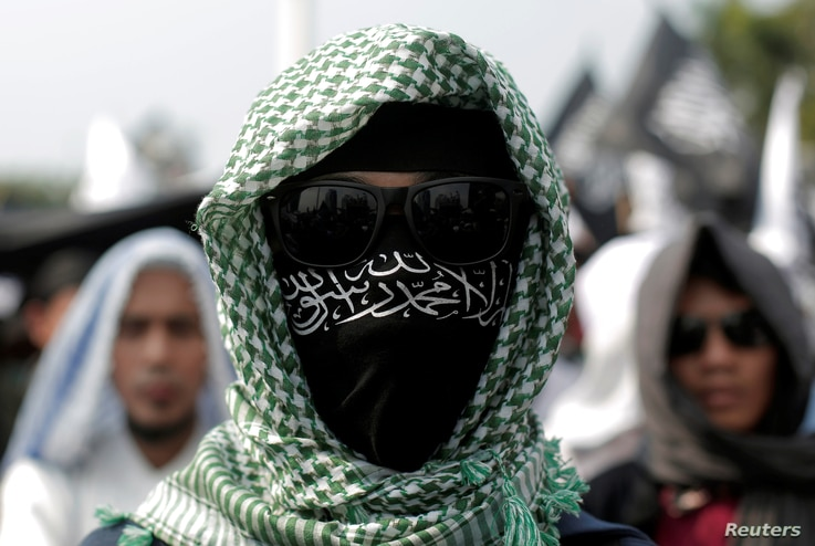 An Islamic group member covers his face with Hizbut Tahrir flag during a protest against the decree allowing the government to disband organizations deemed to run counter to the secular state, in Jakarta, Indonesia, July 28, 2017.