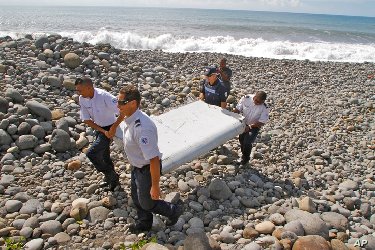 French police officers carry a piece of debris from a plane in Saint-Andre, Reunion Island, July 29, 2015.