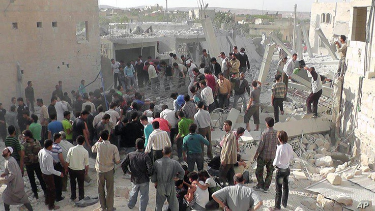 Syrian citizens gather to rescue people from under the rubble of a building that was destroyed from a Syrian force airstrike, at Kfar Nebel town, October 18, 2012.
