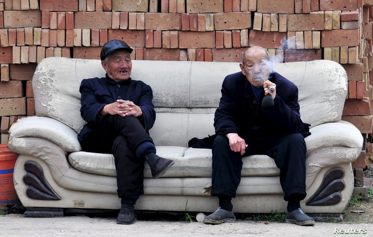 An elderly man (R) smokes a pipe as he chats with another man on a sofa in front of piles of bricks in Yongji, Shanxi province April 11, 2015. China's state pension funds will likely have a funding gap in future due to growing obligations, Vice Finan...