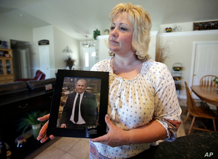 FILE - Laurie Holt holds a photograph of her son at her home, in Riverton, Utah, on July 13, 2016. At a press conference Tuesday, attorney Jeanette Prieto said Holt was being mistreated in violation of  international treaties.