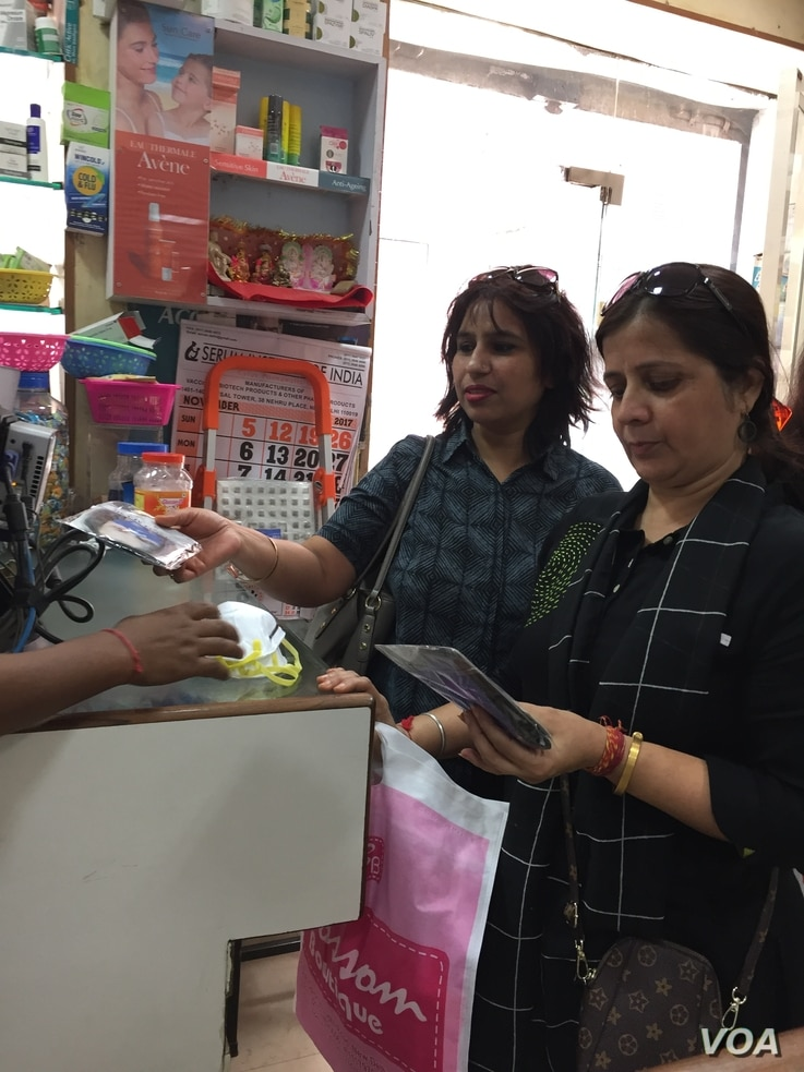 Poonam Sharma, right, looks at masks which many city residents have been purchasing in recent days. (A. Pasricha/VOA)
