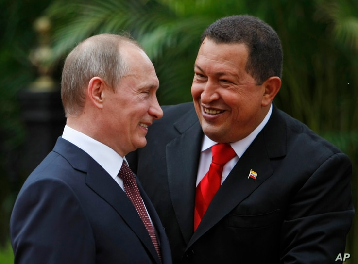 Venezuela's President Hugo Chavez, right, and Russia's Prime Minister Vladimir Putin speak during a welcoming ceremony at Miraflores Presidential Palace in Caracas, Friday, April 2, 2010