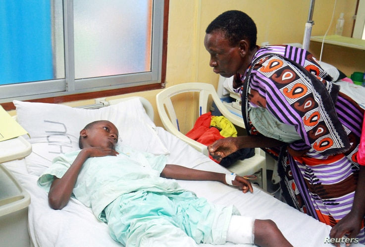 A woman talks to a child injured when Italian volunteer was seized in Chakama trading centre of Magarini, as he receives treatment at the Malindi district hospital in Malindi, Kenya, Nov. 21, 2018.