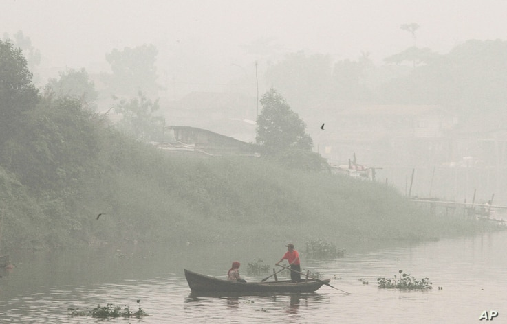 A man rows a boat on Siak River as thick haze from wildfires blanket the city in Pekanbaru, Riau province, Indonesia, Oct. 5, 2015.