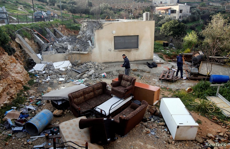 Palestinians check the damages after Israeli forces demolished a house in the village of Al-Walaja near Bethlehem, in the Israeli-occupied West Bank February 11, 2019.