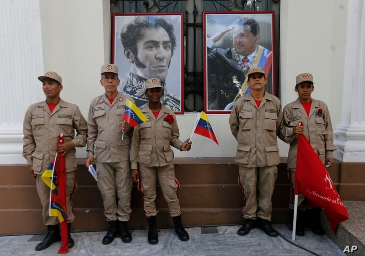 Militia members pose for a photo next to images of Venezuelan independence hero Simon Bolivar, left, and the late President Hugo Chavez, outside Venezuela's National Assembly, in Caracas, Venezuela, Aug. 4, 2017.