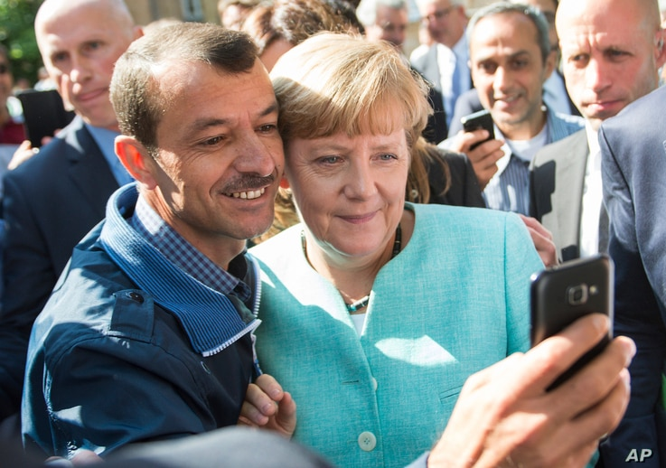 German chancellor Angela Merkel poses for a selfie with a refugee in a facility for arriving refugees in Berlin, Sept. 9, 2015.