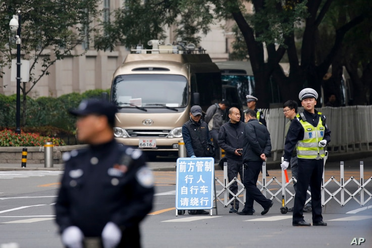 Policemen and security personnel stand guard on a closed road at the entrance to the Jingxi hotel where Communist Party Central Committee members gathered in Beijing, China, Oct. 24, 2016.