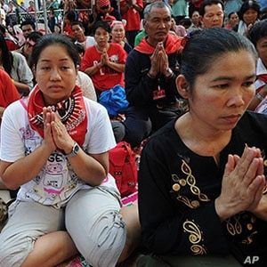 Thai 'Red Shirt' anti-government protesters pray during a ceremony to mark the 60th Coronation Day for King Bhumibol Adulyadej, inside their fortified camp in the financial central district of Silom in downtown Bangkok, 05 May 2010