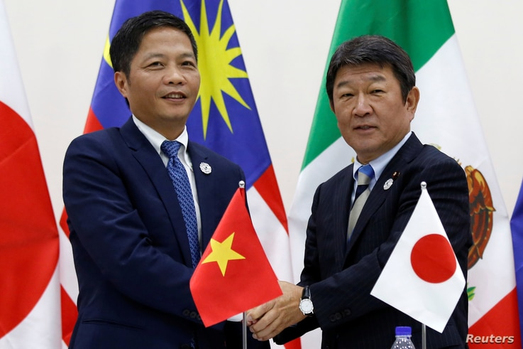 Vietnam's Industry and Trade Minister Tran Tuan Anh, left, and Japan's Minister of Economic Revitalization Toshimitsu Motegi shake hands after a news conference on the Trans Pacific Partnership (TPP) Ministerial Meeting during APEC 2017 in Danang, Vi...