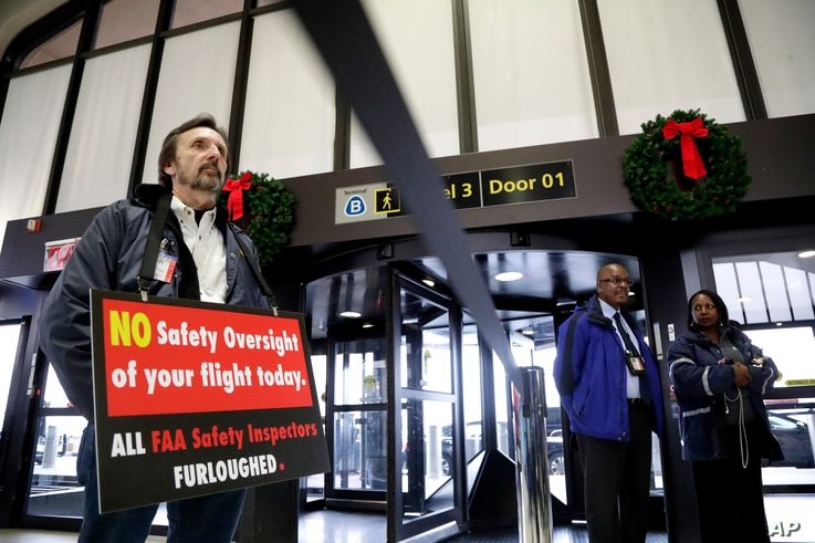 Federal Aviation Administration employee Michael Jessie, who is currently working without pay as an aviation safety inspector for New York international field office overseeing foreign air carriers, holds a sign while attending a news conference at N...