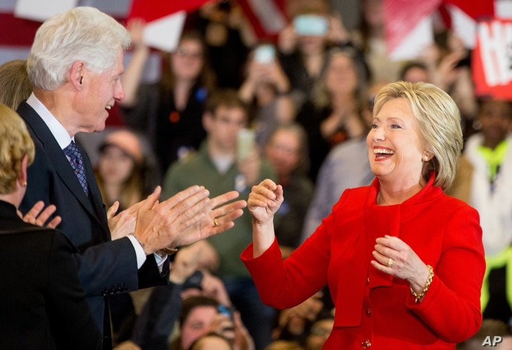 Democratic presidential candidate Hillary Clinton, accompanied by her husband, former President Bill Clinton, arrives at her caucus night rally at Drake University in Des Moines, Iowa, Feb. 1, 2016.