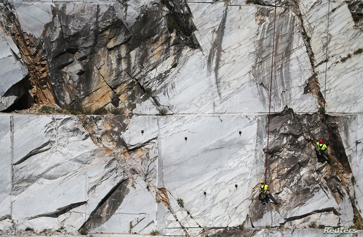 """Workers known as """"Tecchiaioli"""" examine marble at the Cervaiole quarry on Monte Altissimo in the Apuan Alps, Tuscany, Italy, July 18, 2017."""