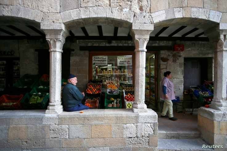 FILE - An old man rests under the medieval arches in the old city of Besalu, near Girona, in the northeastern region of Catalonia, Spain, April 5, 2014.