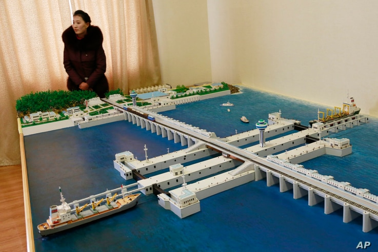 A guide stands next to a model of the West Sea Barrage in Nampo, North Korea, Feb. 2, 2019. North Korea is exploring alternative energy sources.