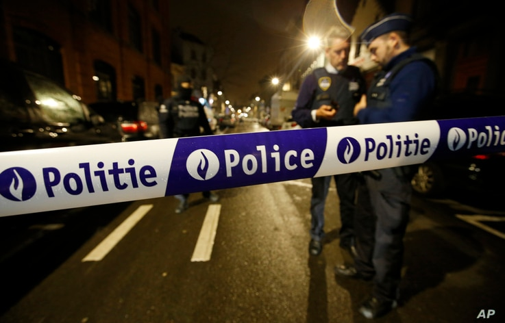 Police guard a check point during a police raid in the suburb of Schaerbeek in Brussels, March, 24, 2016.