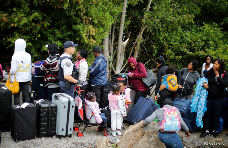 A Royal Canadian Mounted Police (RCMP) officer announces to a group of asylum seekers that identified themselves as from Haiti, that they will be crossing illegally into Canada as they wait in line to to enter at the US-Canada border in Champlain, Ne...