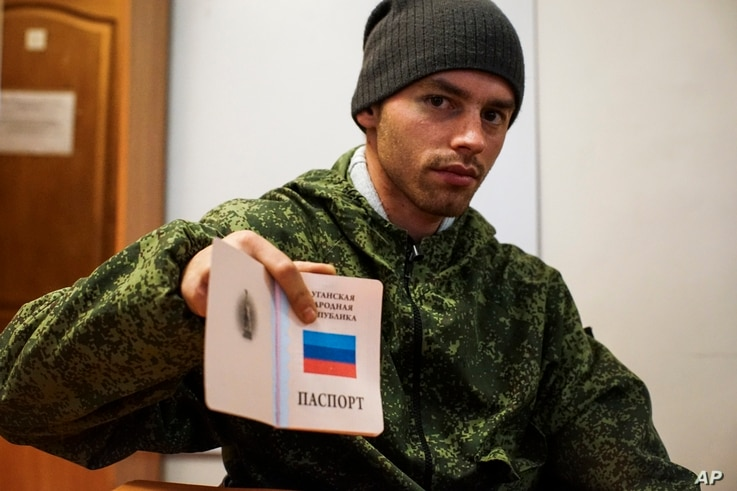 FILE - A young Russia-backed rebel shows a passport of self-proclaimed Luhansk Peoples Republic.