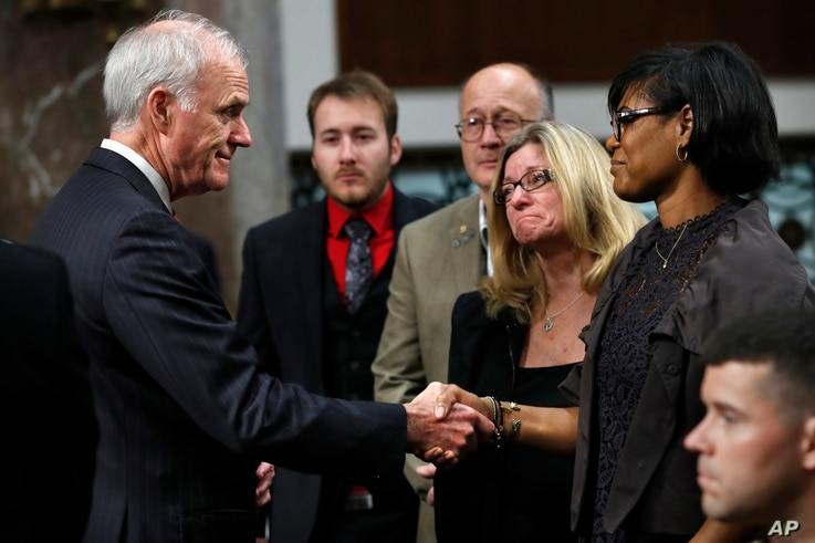 Secretary of the Navy Richard Spencer, left, shakes hands with Rachel Eckels, right, who lost her son, Navy Information Systems Technician Timothy Eckels, 23, of Manchester, Md., on the USS McCain collision, before a Senate Armed Services Committee h...