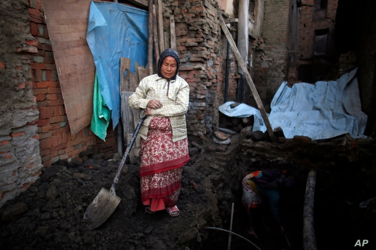 Nhuchhe Laxmi Prajapati digs the foundation of her house, which was damaged by the 2015 earthquake in Bhaktapur, Nepal, Jan. 4, 2017. Nhuchhe took out a loan of $10,000 from a local money lender and has no clue how much the interest is or how she is...