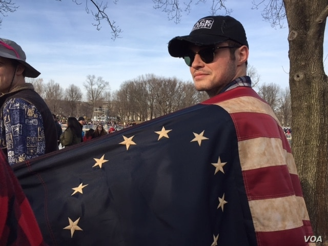 """Some wore old-fashioned flags, others wore red """"Make America Great Again"""" hats to hear the president elect's first greeting of the inauguration. (C. Presutti/VOA)"""