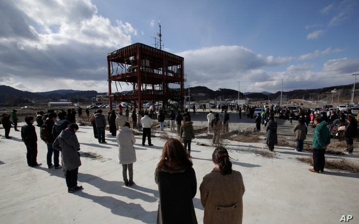 Gathering around what is left of a disaster control center devastated by the March 11, 2011 earthquake and tsunami, people bow their heads in a moment of silence, Minamisanriku, Miyagi prefecture, Japan, March 11, 2013.