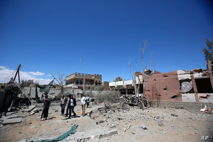 Yemeni people inspect the damage after an airstrike by Saudi-led coalition in Sana'a, Yemen, Saturday, Feb. 27, 2016.