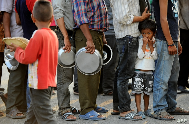 TOPSHOTSNepalese people queue to receive food and goods at a relief camp for survivors of the Nepal earthquake in Kathmandu on May 19, 2015. Nearly 8,500 people have now been confirmed dead in the disaster, which destroyed more than half a million ho...