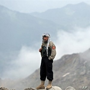 An Afghan security man stands near the mountains where an Afghan Pamir Airways plane is believed to have crashed in the Salang pass, north of Kabul, 17 May 2010