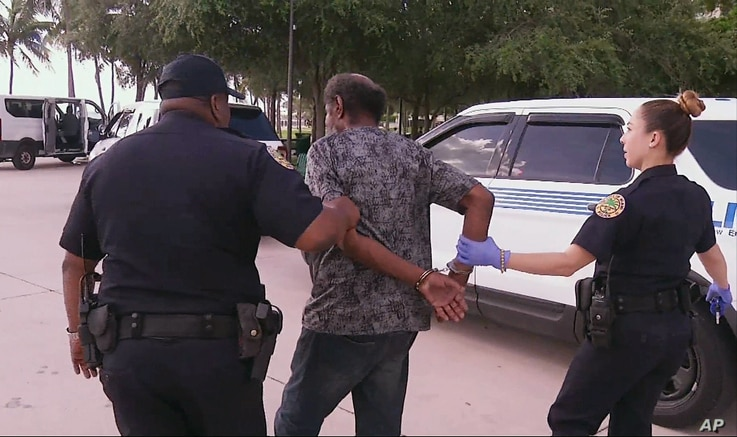 In this frame made from video Sept. 8, 2017, officials in Miami detain a homeless person ahead of powerful Hurricane Irma. Officials detained several people for admission to a psychiatric ward because they suspected mental illness.