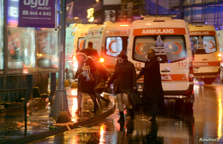 People run from a nightclub where a gun attack took place during a New Year party in Istanbul, Jan. 1, 2017.