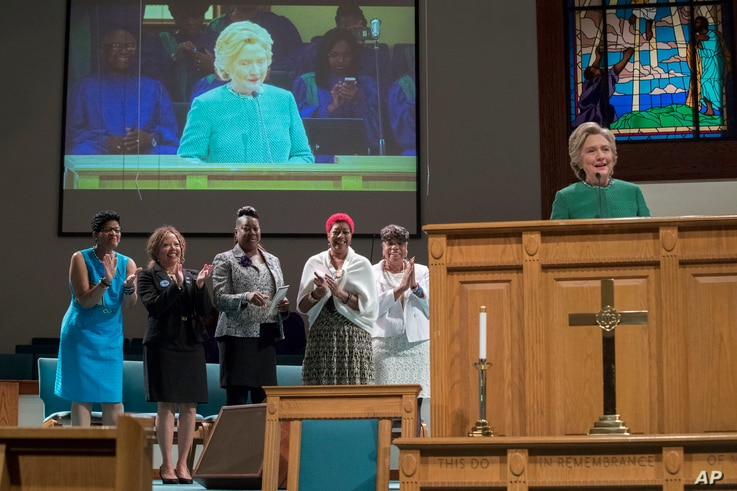 Democratic presidential candidate Hillary Clinton is joined by mothers of black men who died from gun violence, as she speaks during Sunday service at Union Baptist church, Sunday, Oct. 23, 2016, in Durham, N.C.