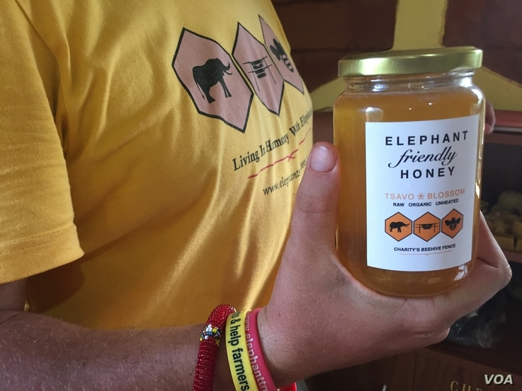Elephants and Bees Project research center coordinator Matthew Rudolph shows a jar of honey that came from beehives at Charity Mwangome's farm, in Taita-Taveta area, Kenya, April 19, 2016.