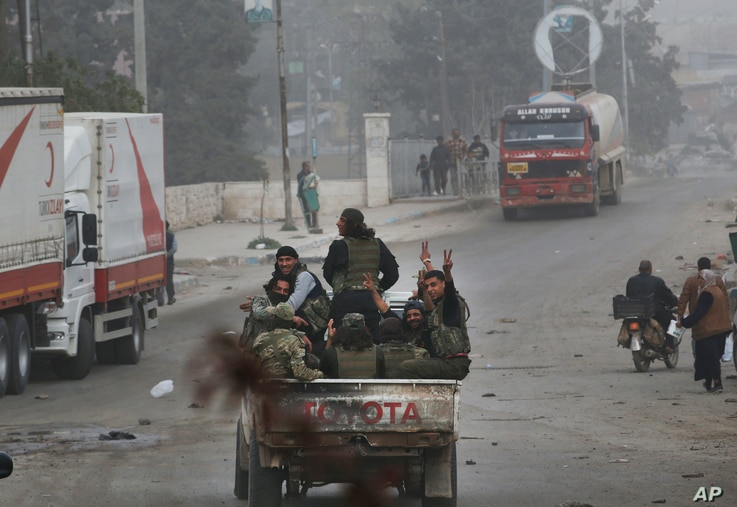 Turkey-backed opposition fighters of the Free Syrian Army flash the V-sign from atop a pick-up truck as they patrol the northwestern city of Afrin, Syria, during a Turkish government-organized media tour into northern Syria, March 24, 2018.