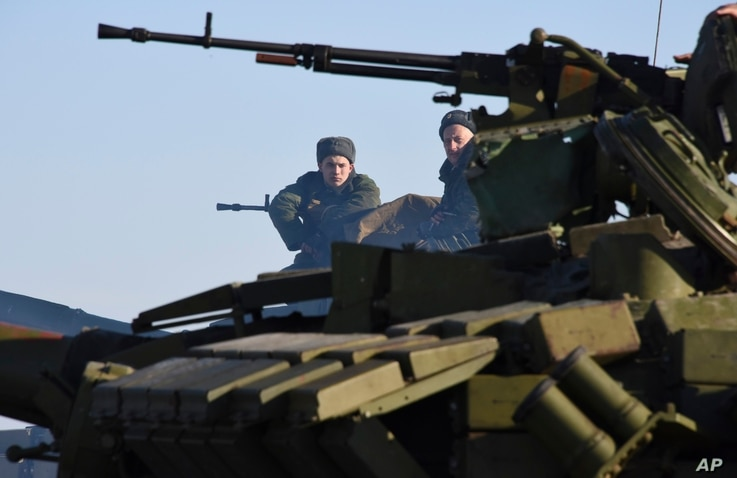 Russian-backed separatist sit on top a tank at the check-point north of Luhansk, Eastern Ukraine, Jan. 14, 2015.