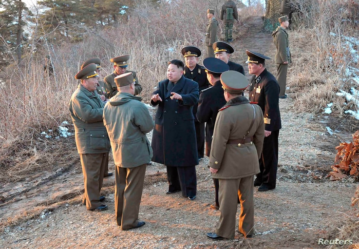 North Korean leader Kim Jong-Un talks with generals as soldiers of the Korean People's Army take part in landing and anti-landing drills in eastern North Korea, March 25, 2013.