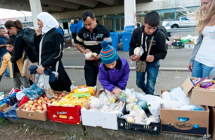 Migrants who arrived from Hungary receive food at a collection point in the truck parking lot of the former border station on the Austrian side of the Hungarian-Austrian border near Nickelsdorf, Sept. 21, 2015.