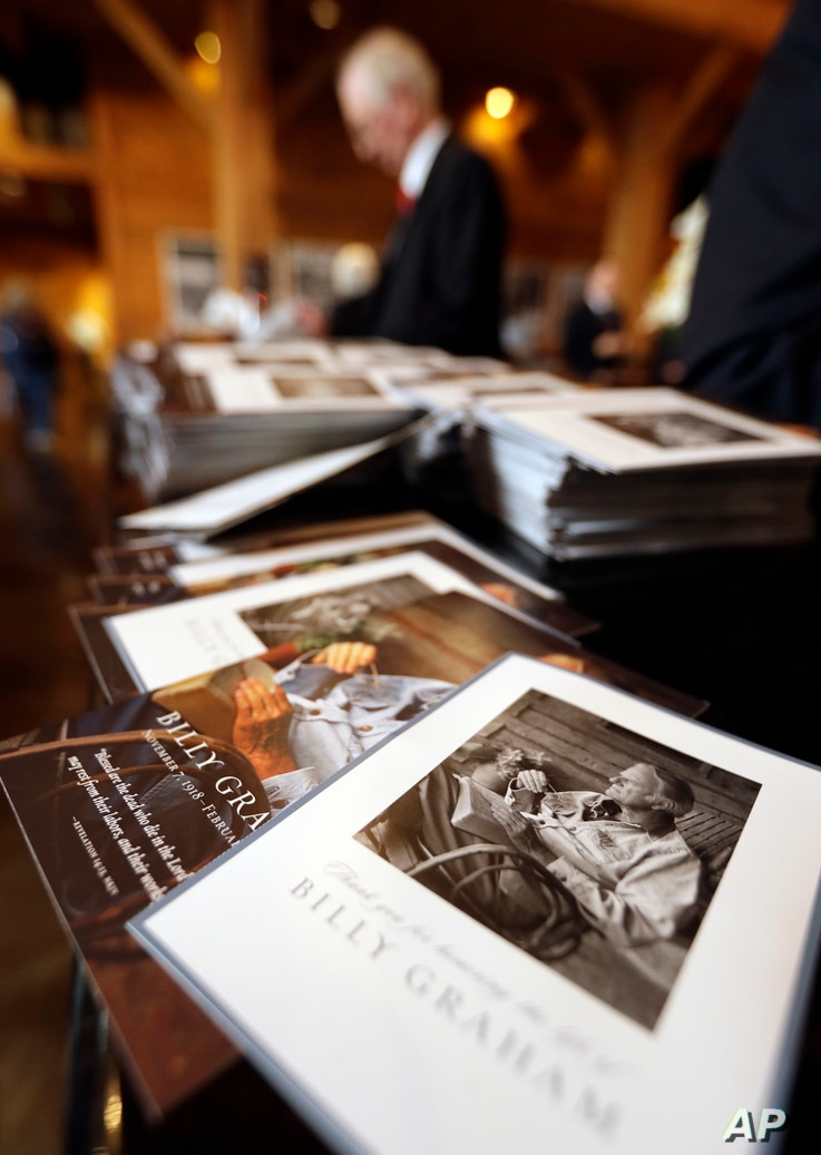 A stack of remembrance brochures are placed at the entrance as people come to pay respects to Billy Graham during a public viewing at the Billy Graham Library in Charlotte, N.C., Feb. 26, 2018.