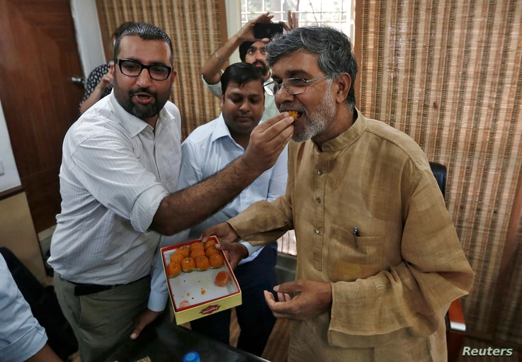A well-wisher offers sweets to Indian children's right activist Kailash Satyarthi, named to share the Nobel Peace Prize, at his New Delhi office Oct. 10, 2014.