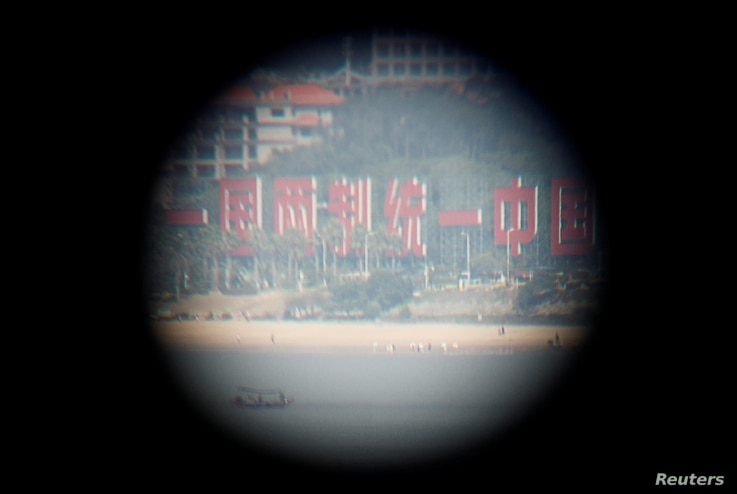 "China's banner reading ""One Country, Two Systems, One Unified China"" is seen through a tourist's binoculars from a former military fort, ahead of the 60th anniversary of Second Taiwan Straits Crisis against China, in Lieyu island, Kinmen county, Taiw..."